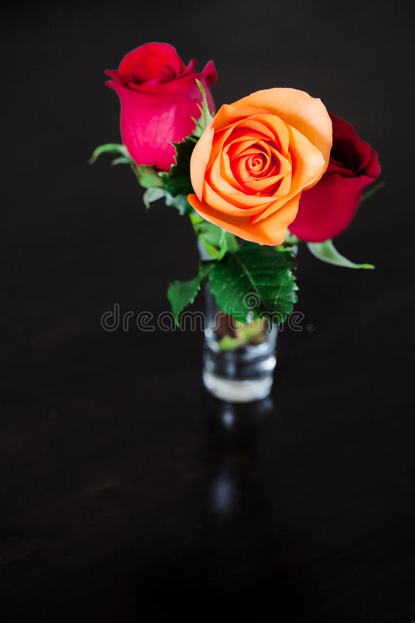 Цветастые розы в вазе на деревянной таблице стоковая фотография rf