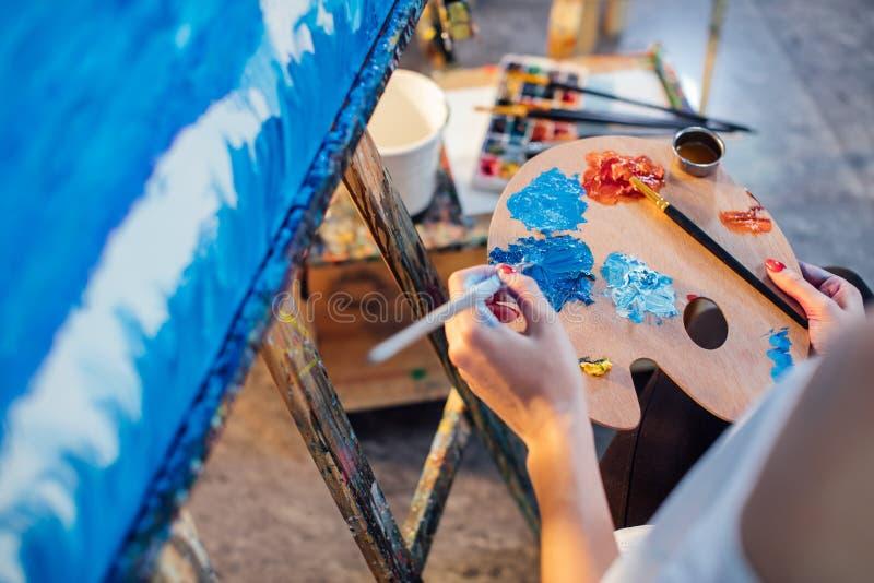 Цвета масла художника женщины смешивая на палитре держа в ее руке стоковая фотография