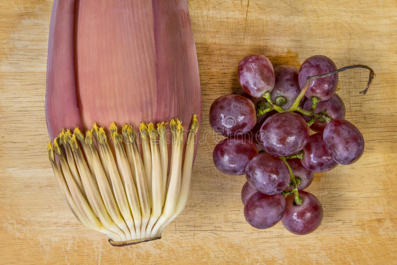 Цветение банана и фиолетовая виноградина на древесине стоковые изображения rf