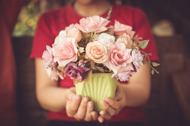 Цветение влюбленности цветка владением руки женщин крупного плана розовое стоковое изображение rf