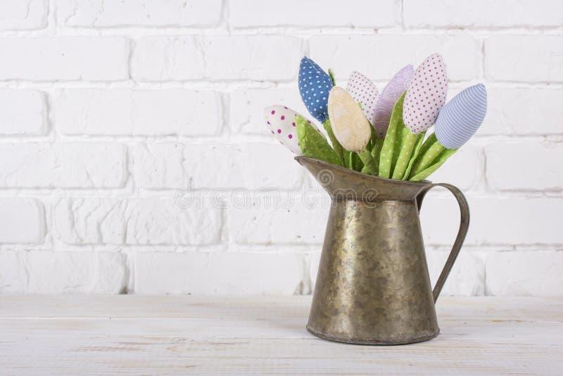 Цветет тюльпаны сделанные из ткани в кувшине вазы металла задняя часть белизны стоковые фото