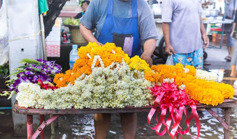 Цветки гирлянды продавая в таблице ходят по магазинам в тайском идя рынке стоковые фотографии rf