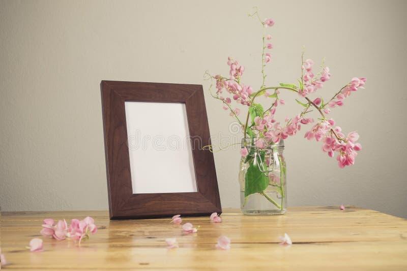Цветки и белая рамка фото на деревянном столе стоковые изображения rf