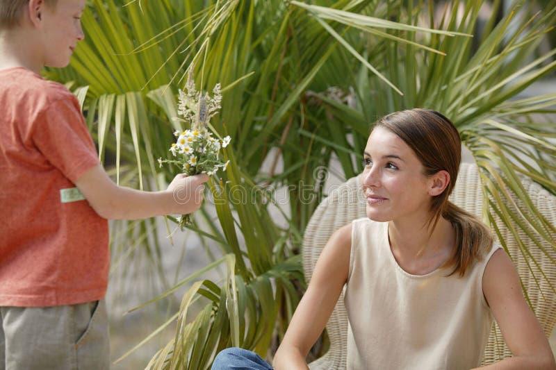 цветки мальчика давая к детенышам женщины стоковые фото