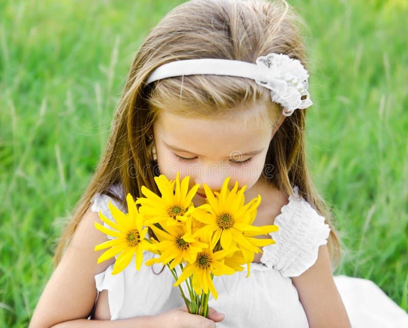 Цветки милой маленькой девочки пахнуть на лужке стоковые изображения rf