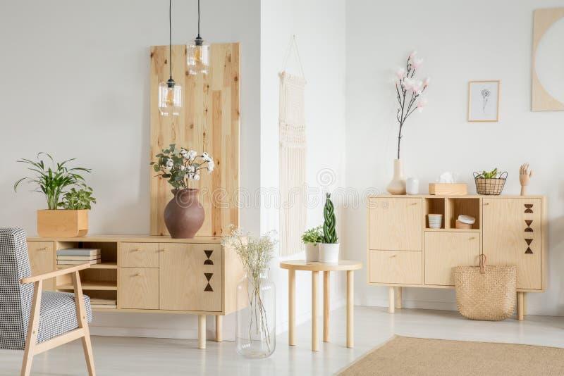 Цветки на деревянном кухонном шкафе в белом интерьере живущей комнаты с ar стоковое изображение