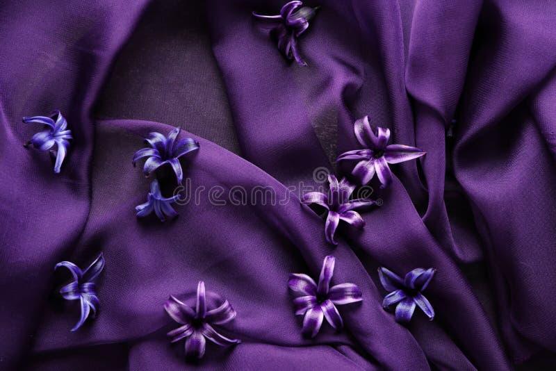 Цветки на пурпурной ткани стоковые изображения