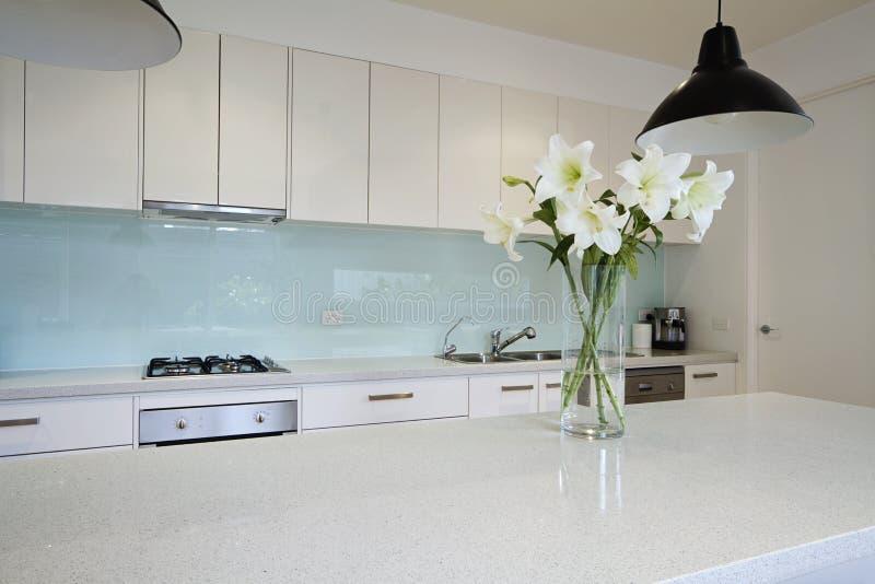 Цветки на современном стенде кухни стоковые фото