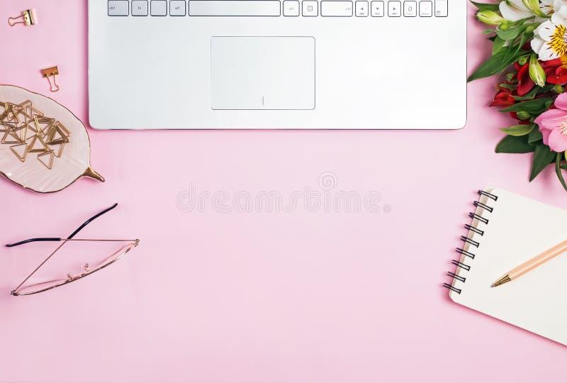 Цветки, ноутбук и канцелярские принадлежности на розовой предпосылке стоковая фотография