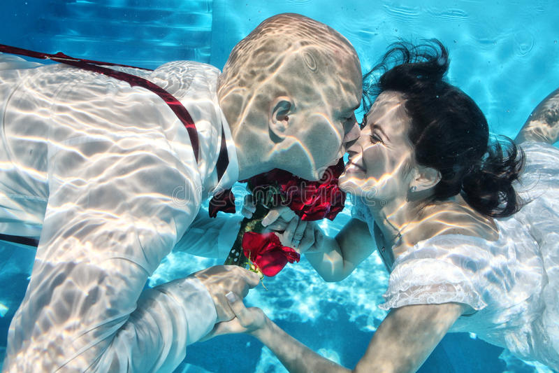 Цветки подводной свадьбы жениха и невеста целуя ныряя красные стоковые изображения