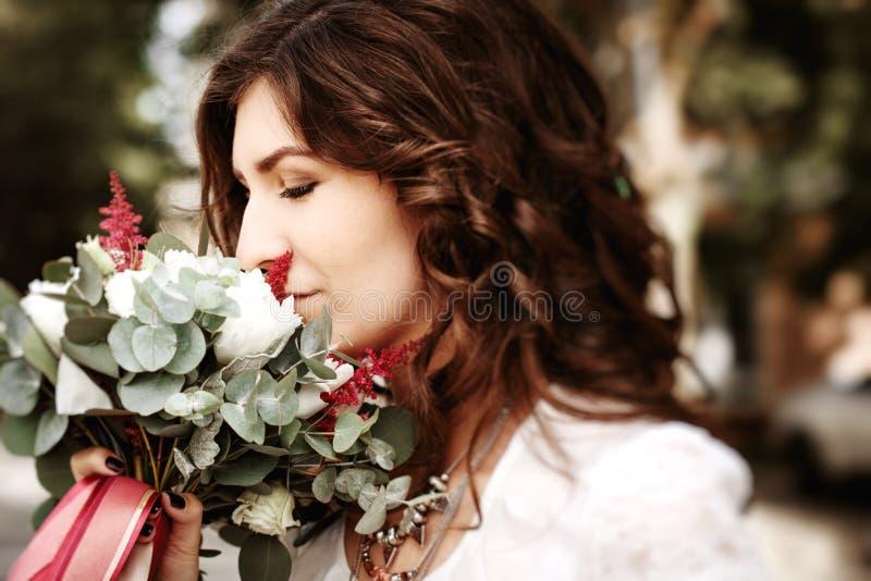 Цветки свадьбы красивой женщины пахнуть стоковое изображение rf