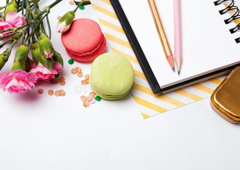 Цветки, macarons, бумажный блокнот и pensils стоковое фото