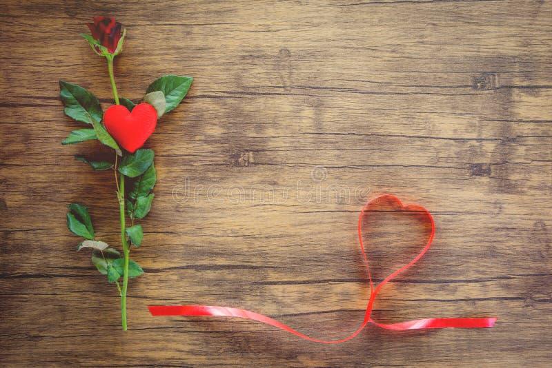 Цветок красной розы дня Святого Валентина на деревянном красном сердце с розами и красном сердце ленты на космосе экземпляра взгл стоковое изображение