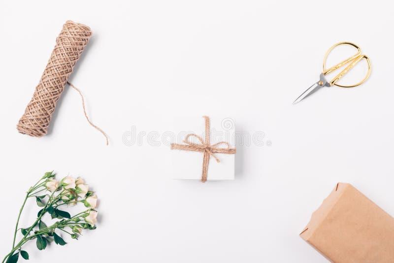 Цветочная композиция небольшой присутствующей коробки, подняла ветвь, шпагат и ножницы, взгляд сверху Плоское положенное располож стоковые фотографии rf