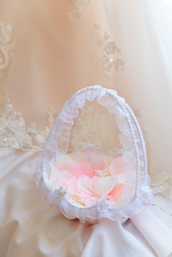Цветочные лепестки в кружевной корзине на свадебном платье стоковая фотография rf
