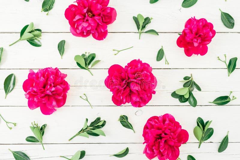 Цветочный узор пиона и листьев на белой деревянной предпосылке Плоское положение, взгляд сверху Картина сделанная из цветков стоковые изображения