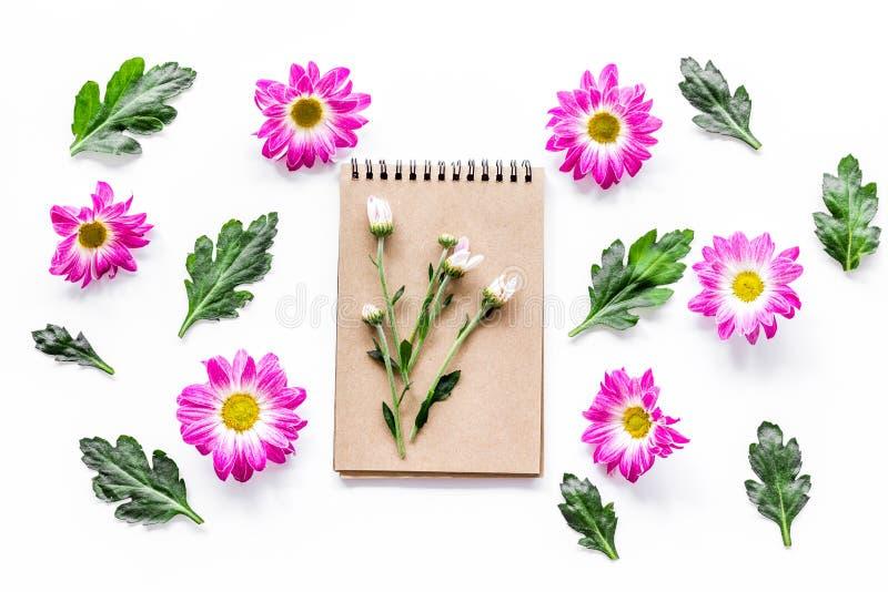 Цветочный узор с розовыми цветками, листьями зеленого цвета и тетрадью на белом взгляд сверху предпосылки стоковые изображения rf