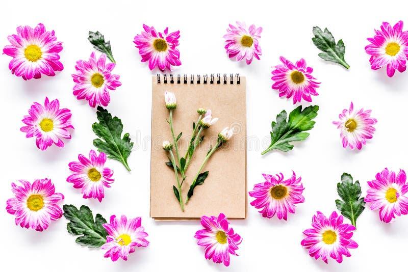 Цветочный узор с розовыми цветками, листьями зеленого цвета и тетрадью на белом взгляд сверху предпосылки стоковые фотографии rf
