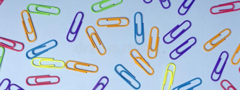 Цвет закрепляет минимальную концепцию Покрашенные бумажные зажимы на покрашенной предпосылке стоковое изображение rf