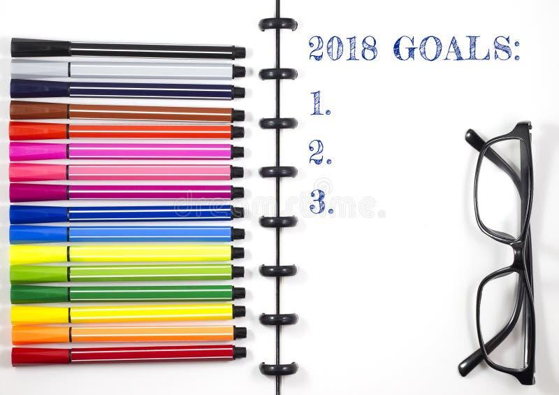 2018 целей отправляют СМС на белом sketchbook с ручкой цвета и наблюдают стекла, взгляд сверху/плоское положение стоковые фото