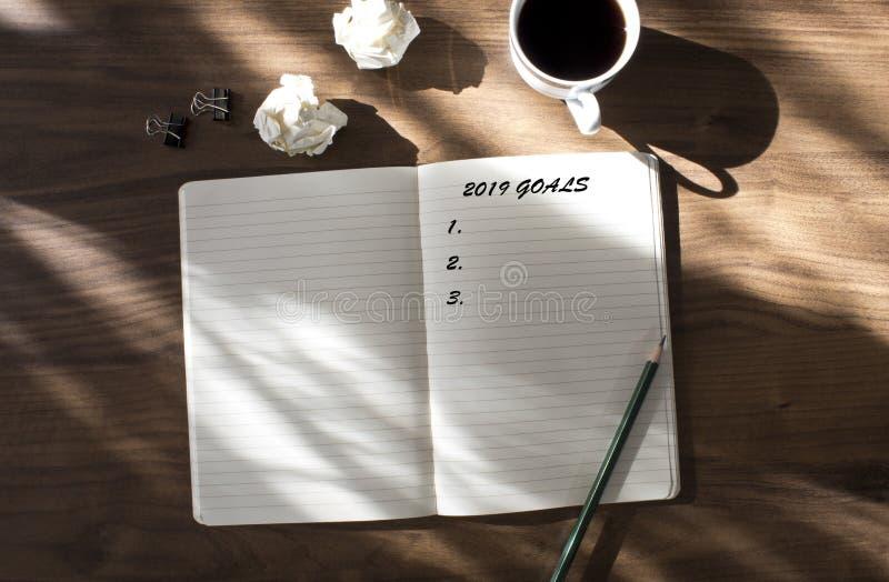 2019 целей перечисляют с тетрадью, чашкой кофе сверх на деревянной предпосылке стоковое изображение