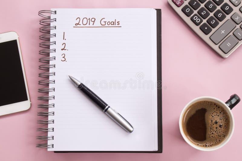 2019 целей перечисляют с тетрадью, чашкой кофе сверх на розовой предпосылке стоковые изображения rf