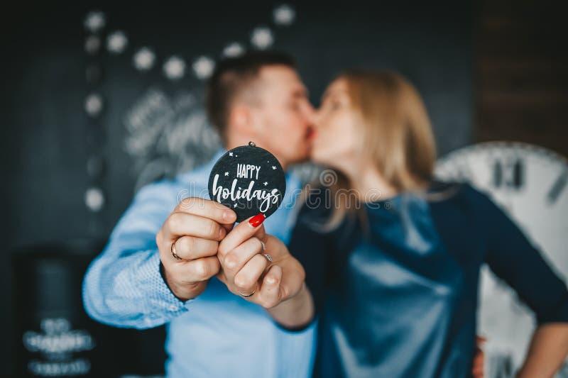 Целовать пар держа деревянный круглый знак стоковая фотография