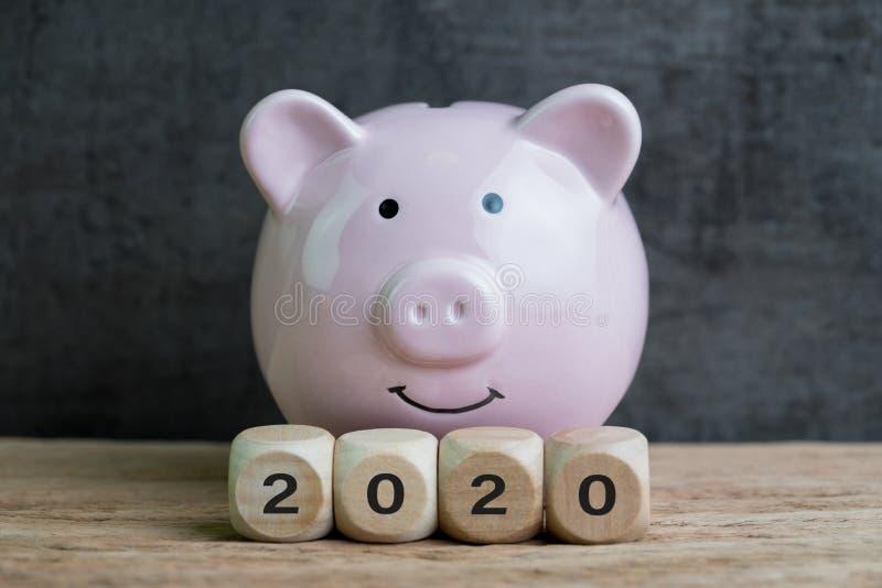 Цель года 2020 финансовая, бюджет или вклад, счастливая усмехаясь розовая копилка с деревянным блоком куба с 2020 на таблице и стоковая фотография rf