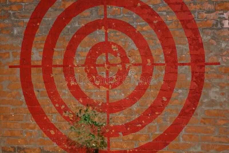 Цель на красной кирпичной стене graffiti Они ударили цель с веником Части летают стоковые фотографии rf