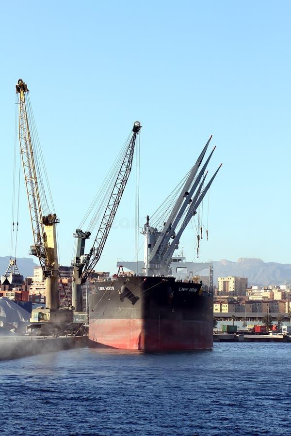 Цемент загрузки СТРЕЛКИ судно-сухогруза LAWIN с кранами в порте Аликанте стоковое изображение