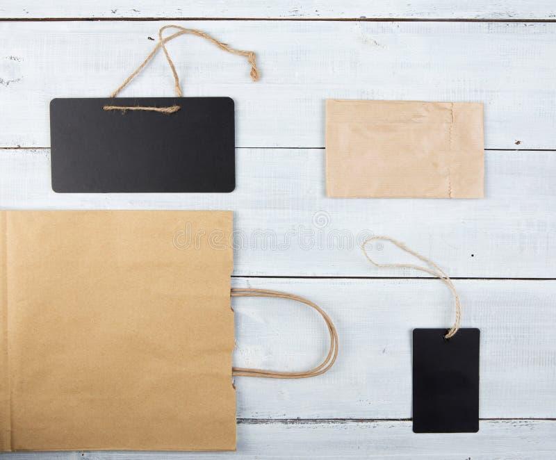 Ценники и бумажная хозяйственная сумка на деревянном столе стоковые изображения rf