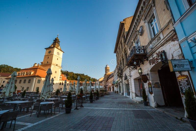 Центральная площадь города (Piata Sfatului) с взглядом восхода солнца утра башни залы городского совета, положением Brasov, Транс стоковое изображение