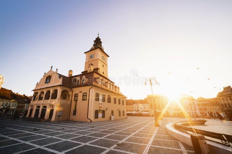 Центральная площадь города (Piata Sfatului) с взглядом восхода солнца утра башни залы городского совета, положением Brasov, Транс стоковое изображение rf