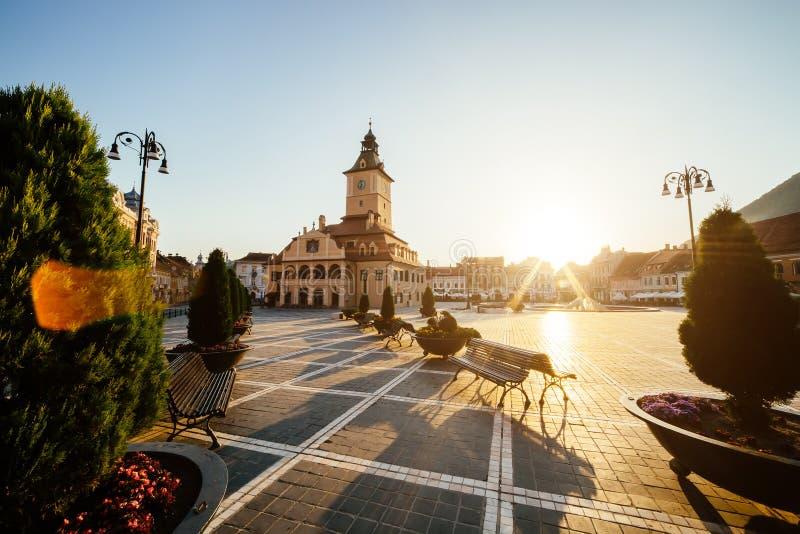 Центральная площадь города (Piata Sfatului) с взглядом восхода солнца утра башни залы городского совета, положением Brasov, Транс стоковые изображения rf