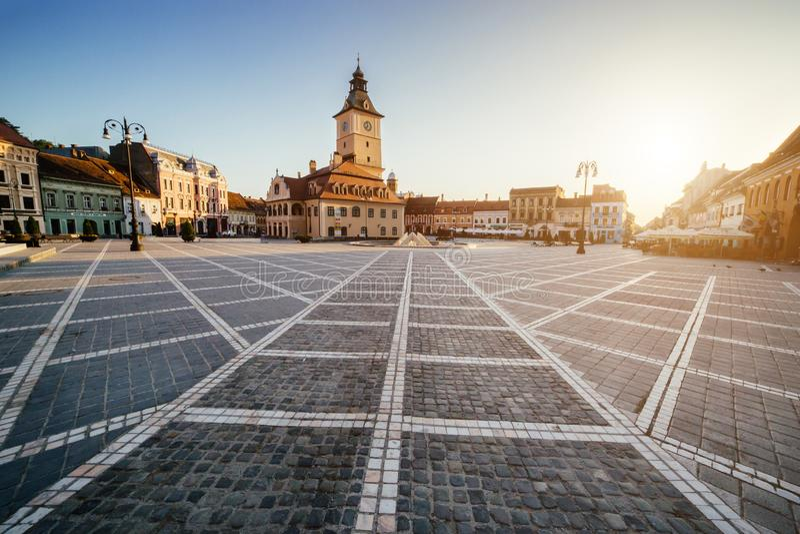 Центральная площадь города (Piata Sfatului) с взглядом восхода солнца утра башни залы городского совета, положением Brasov, Транс стоковая фотография rf