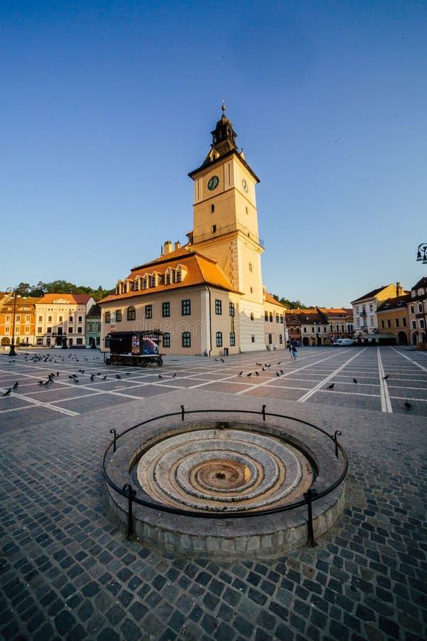 Центральная площадь города (Piata Sfatului) с взглядом восхода солнца утра башни залы городского совета, положением Brasov, Транс стоковые фотографии rf