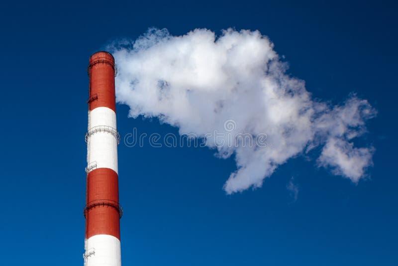Централь жары и силы, курит промышленную печную трубу против ясного голубого неба стоковые изображения