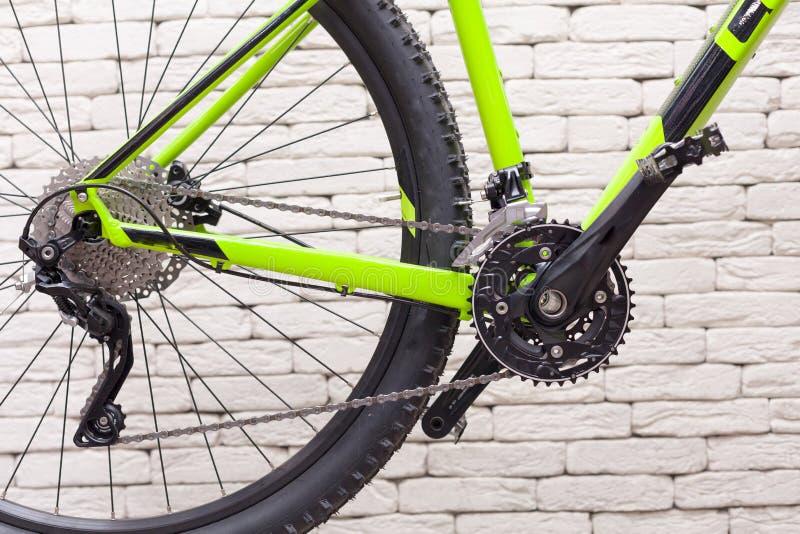 Цепь велосипеда против белой кирпичной стены Цепные колеса велосипеда стоковая фотография rf