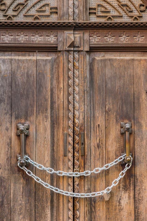 Цепь запирает старую деревянную дверь стоковая фотография