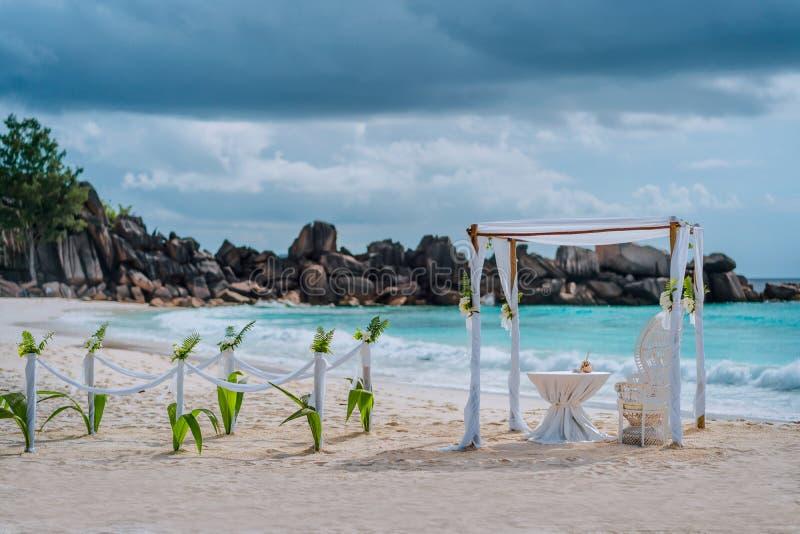 Церемония свода свадьбы на пляже украшенная с белыми цветками на тропическом пляже с белым песком Установка свадьбы рая экзотичес стоковые фото