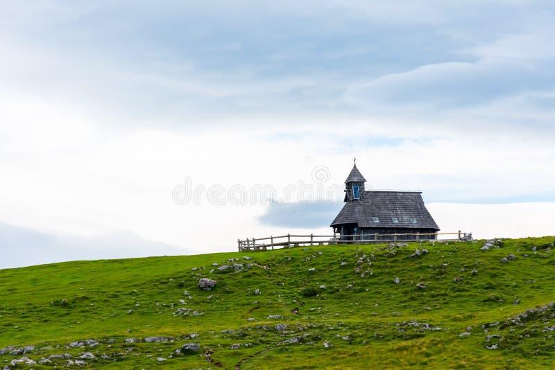Церковь в выгоне Velika Planina плато Словении большом Часовня на холме, символ вероисповедания Зеленый луг и голубое небо с стоковое изображение