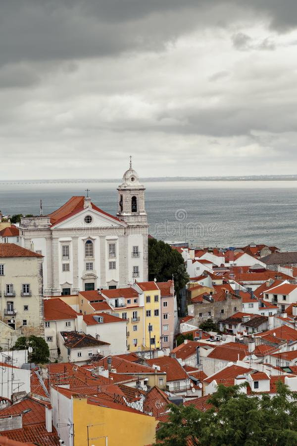 Церковь в Лиссабоне с целью города и моря под облачным небом стоковые изображения