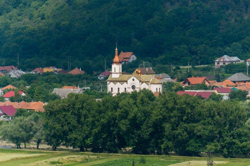Церковь с белыми стенами и шариками куполов с близрасположенными домами в деревне среди деревьев в живописном районе на стоковое фото