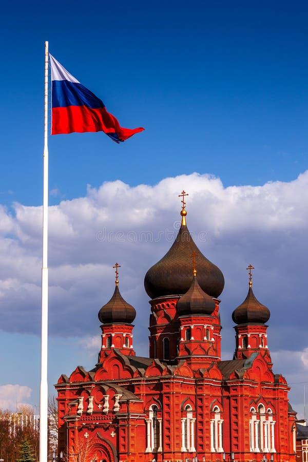 Церковь с черными куполами под флагом России стоковая фотография