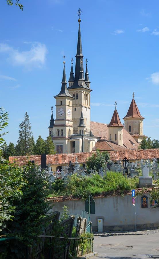 Церковь St Nicholas в Brasov (Kronstadt), Трансильвании (Siebenbuergen), Румынии Башни и тягчайший двор, строб, солнечное голубое стоковое фото