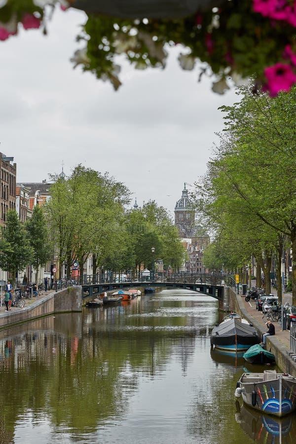 Церковь St Nicholas ориентир Амстердама в Нидерланд, уникальный со сценой города вдоль канала в естественном свете утра стоковое изображение