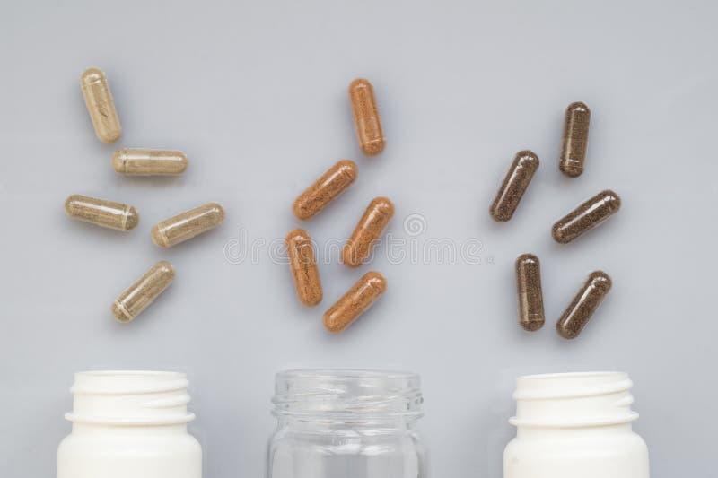 Целебная расслоина капсулы из бутылок 3 пластмасс на ligh стоковая фотография