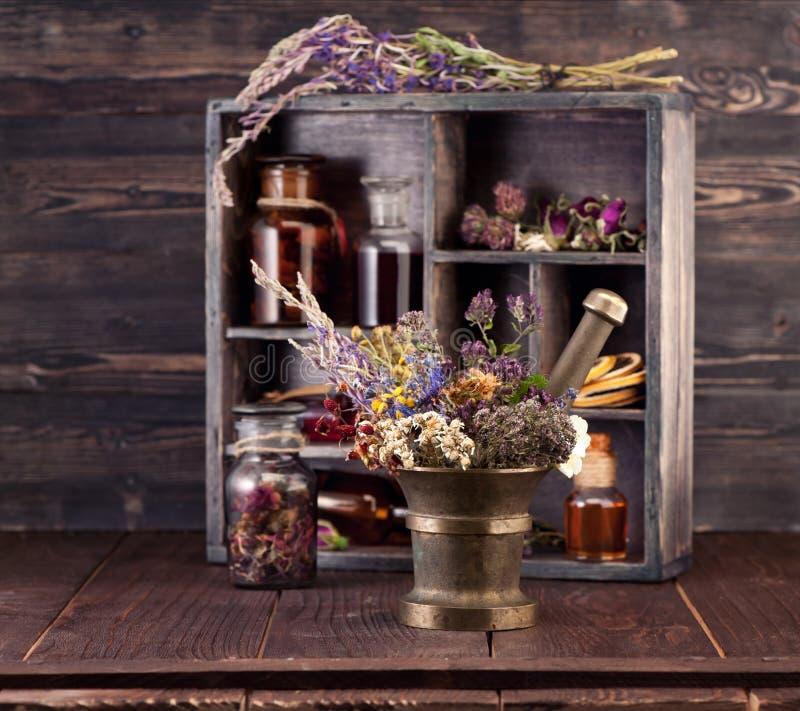 Целебные травы миномет и тинктура бутылок стоковые фото