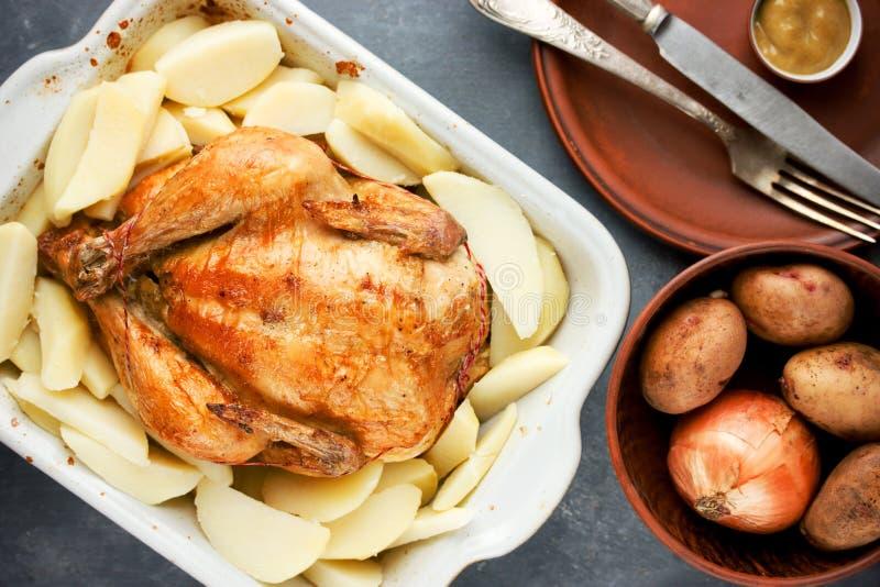 Целый зажарило в духовке цыпленк цыпленок с золотой картошкой гарнированной коркой стоковые фотографии rf