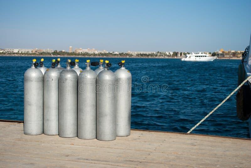 Цилиндры с кислородом для водолазов 10 цилиндров на доке моря кислород для водолазов на пристани Синие цилиндры воды и стали стоковое фото